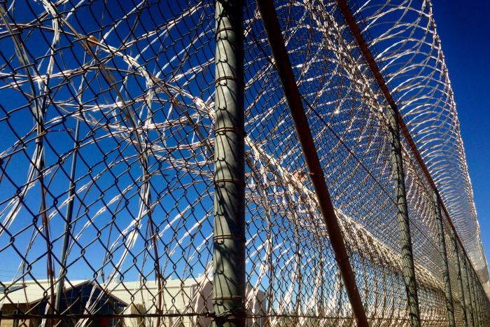 A tall fence with razor wire attached at the bottom and top. Blue sky and some jail buildings in the background.