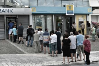 People stand in a queue to use ATM machines to withdraw cash at a bank in Athens