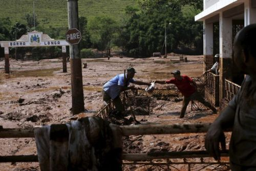 Men clean out a house flooded by mud