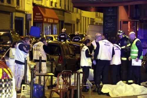 Rescue service personnel working near the covered bodies outside a restaurant following a shooting incident in Paris