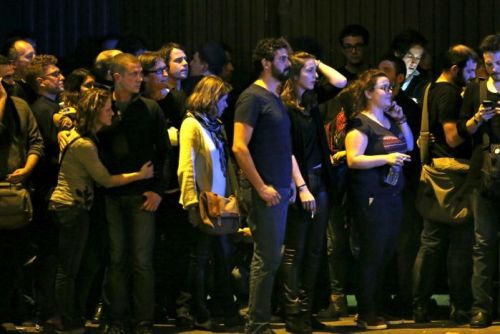 People react as they gather to watch the scene near the Bataclan concert hall