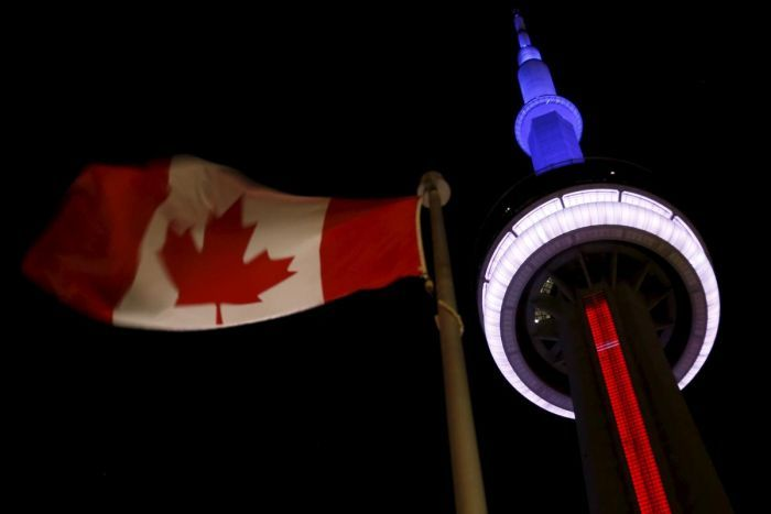 Landmark CN Tower in Toronto lit up in blue, white and red