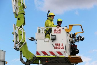 ABC News Canberra journalist Alkira Reinfrank in an aerial appliance which extends up to 44 metres in the air