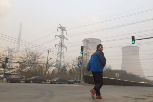 A man walks past a power plant in eastern Beijing.