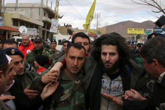 A Lebanese soldier helps a fellow member of the security forces moments after his release.