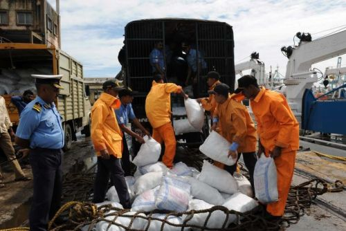 Indian relief workers load supplies for flood victims