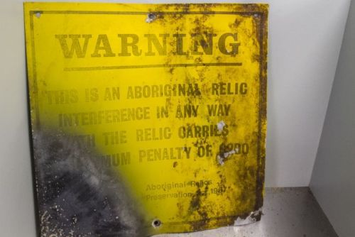 An old sign warning tourists of relics on North Stradbroke Island.