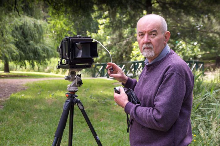 A man stands next to an analogue camera and holds the cord with the button used to take the photograph