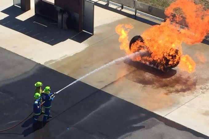 Volunteer fire units practise fighting a gas fire.