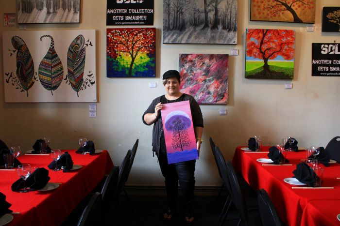 Mackay artist Nekea Blagoev stands inside a Mackay restaurant surrounded by her colourful paintings of trees