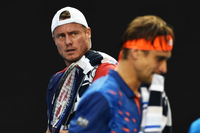 Lleyton Hewitt is in focus as David Ferrer walks in front of him, blurred in the foreground.