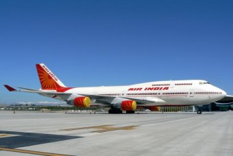An Air India Boeing 747-400 sits taxis on a runway.