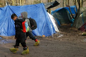 Two children walk past a tent at a muddy asylum seeker camp in northern France.