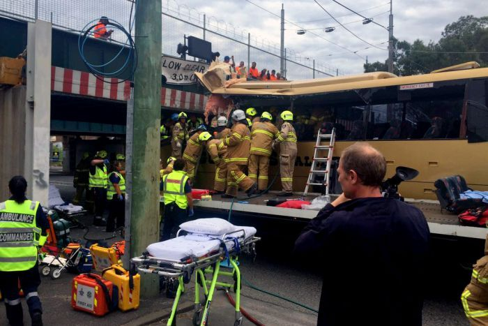 Emergency crews work to free passengers from the bus which is wedged under the bridge.