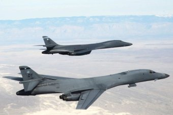 Two B-1B Lancers fly in formation over arid terrain.