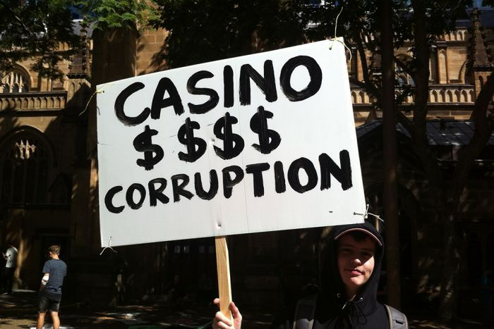 """A young man holds up a sign saying """"Casino $$$ Corruption'"""
