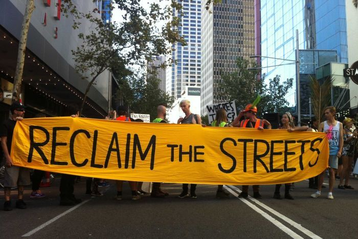 """Protesters hold a sign that reads """"Reclaim the Streets"""" outside Sydney's Star City Casino."""
