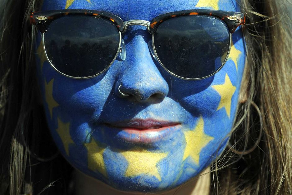A festival-goer with a European flag painted on her face poses for a photograph on day three of the Glastonbury Festival