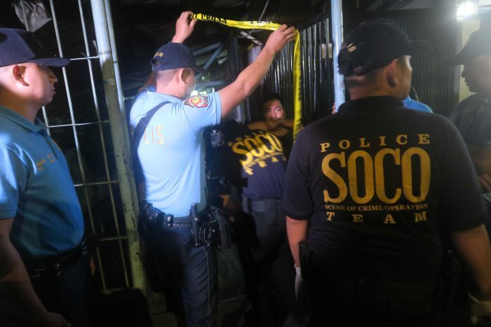 Philippines forensics team moves through yellow tape