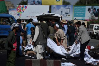 Afghan volunteers carry the bodies of victims at the scene.