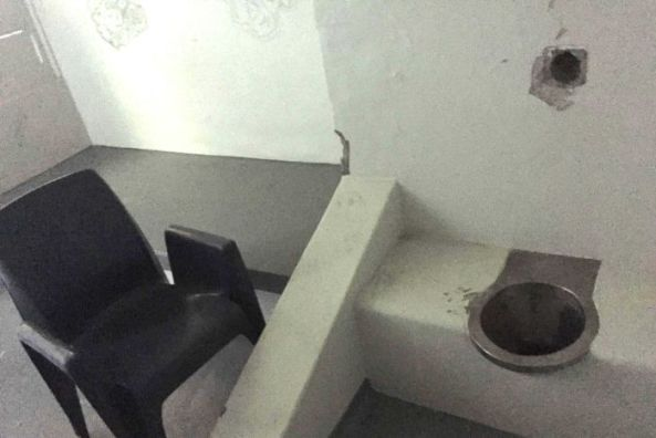 A basic toilet and plastic chair inside a cell in the isolation wing of the Don Dale prison.