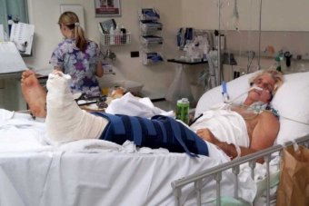 a man laying in hospital bed with foot bandaged, tubes going up his nose.