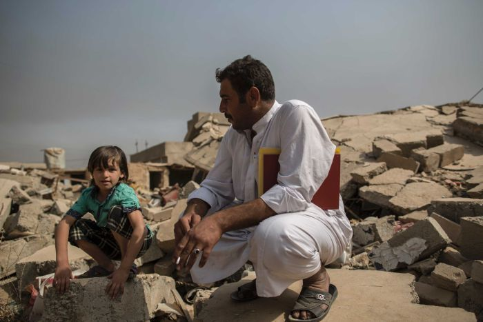 Mosul: father and son sit on the ruins of house in village of Imam Gharbi