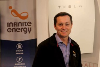 Shane Cremin stands near a tesla power wall battery