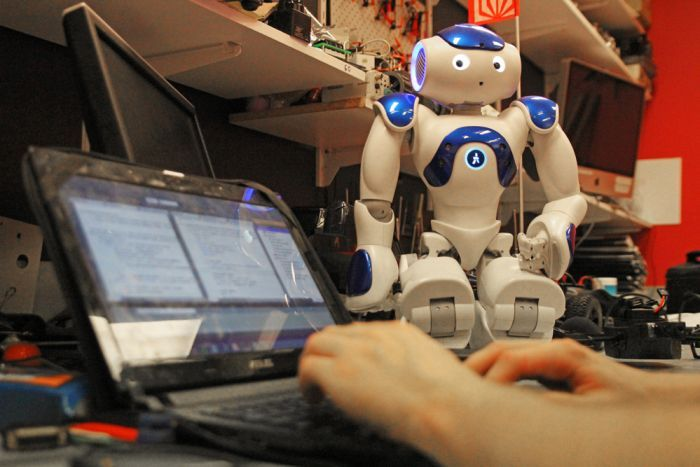 A Nao robot watches a student typing on a laptop