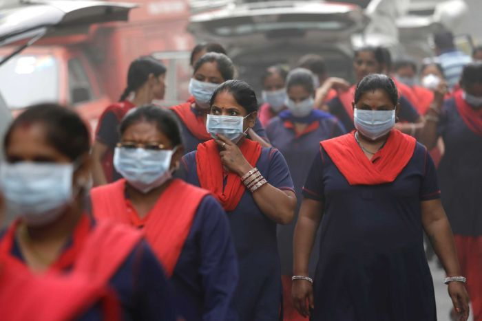 A group of women wearing pollution masks.