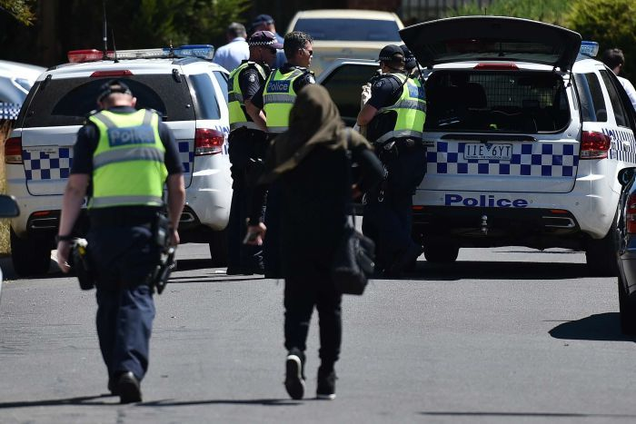 Police with woman at Meadow Heights following raids