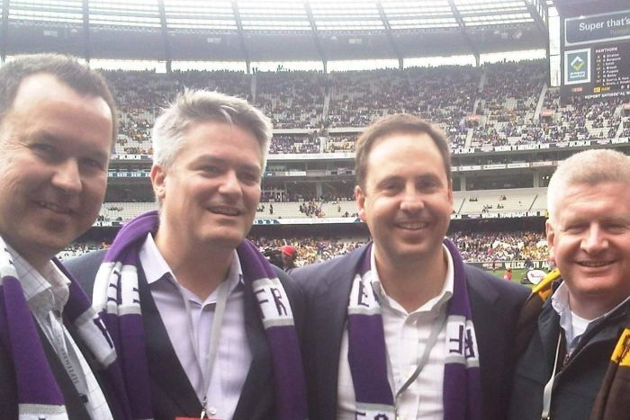 Tasmanian Senator David Bushby, Finance Minister Mathias Cormann and Trade Minister Steve Ciobo at an AFL Grand Final match.
