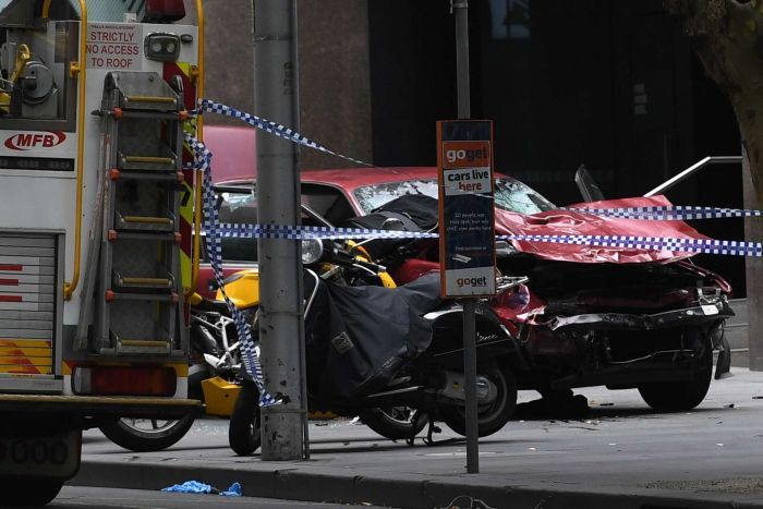 A car is seen crushed and damaged after being driven through busy Bourke St mall.