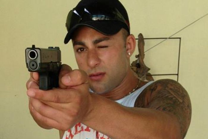 A man points a gun directly at the camera. He is wearing a cap with sunglasses on top, and has one eye closed.
