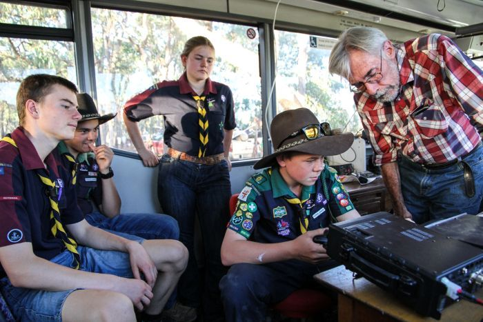 Trainer Tony Falla showing the Castlemaine Venturers how to tune in on the amateur radio equipment  from the inside of a bus.