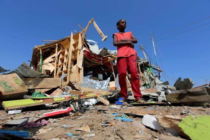 A boy outside the wreckage of his shop in Mogadishu after a bomb blast.