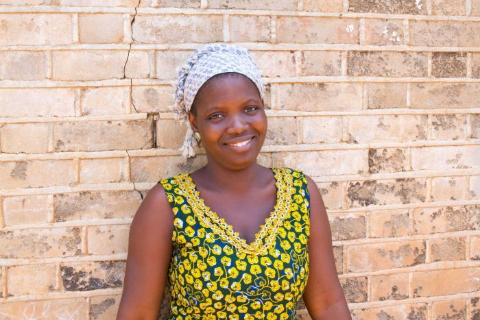 Mariama standing in front of a brick wall smiling.