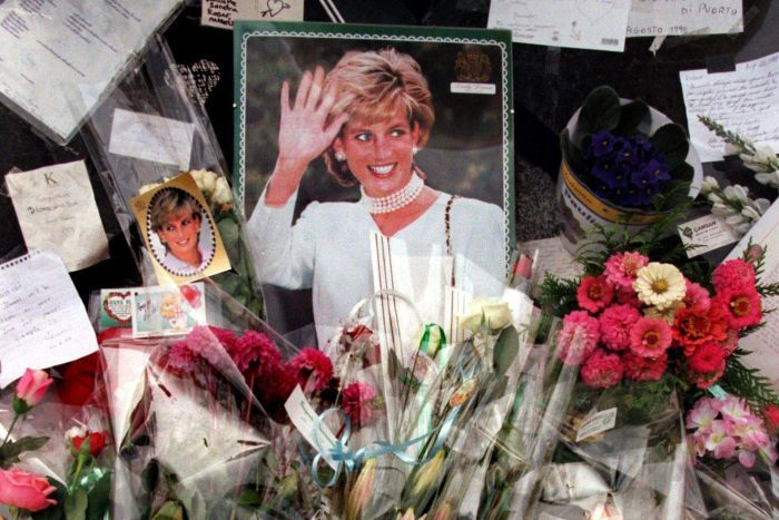 Flowers, photographs, candles and cards are piled up around a photo of Princess Diana.