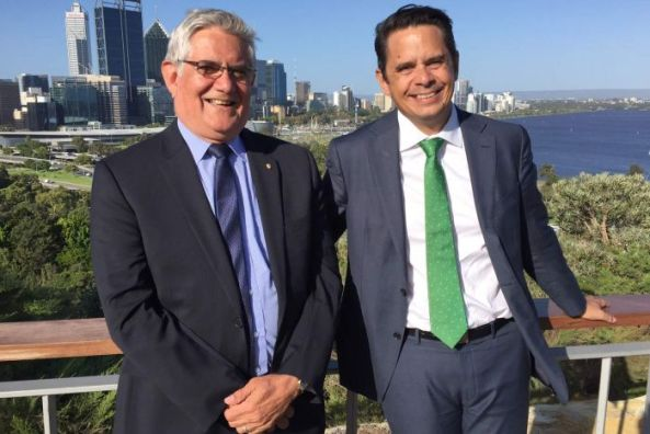 A smiling Ken and Ben Wyatt standing side by side at Kings Park with the Perth city CBD and Swan River in the background.