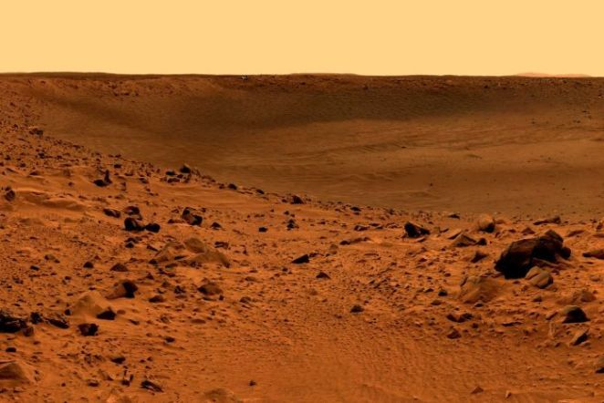 Red dirt and rock dominate this landcape of Mars, and the sky is a light orange