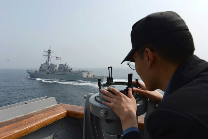 A man looks at the destroyer at a US vessel