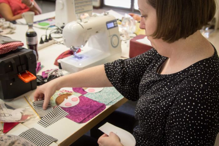 Sarah Mummé works on sewing a soft toy.