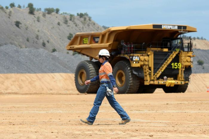 A woman walks past a dump truck at a large mining site.