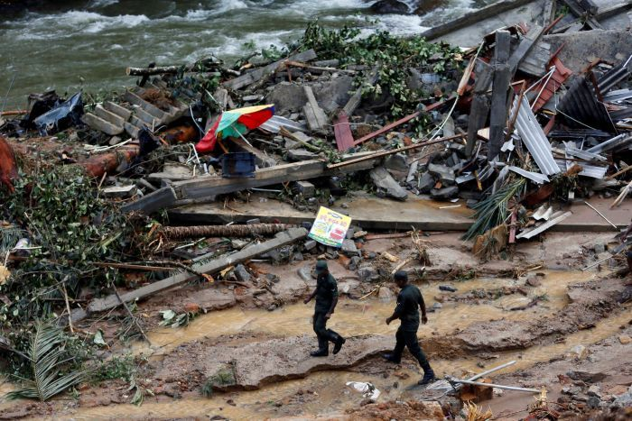 Sri Lankan army soldiers walk past the debris of houses at a landslide site during a rescue mission in Sri Lanka.