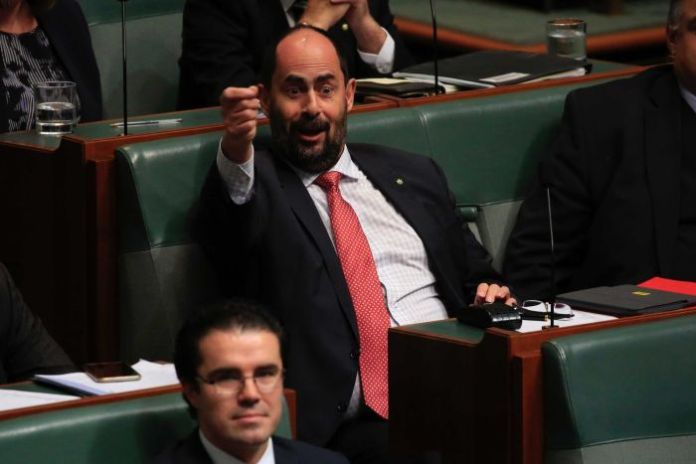 Ross Hart holds his right hand at eye level like a fist, apparently making fun of the opposition during question time.