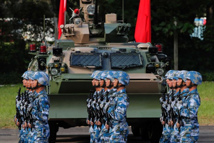 Soldiers in blue and white camo helmets and fatigues march past a tank and Chinese flags, lined up perfectly, and holding guns.