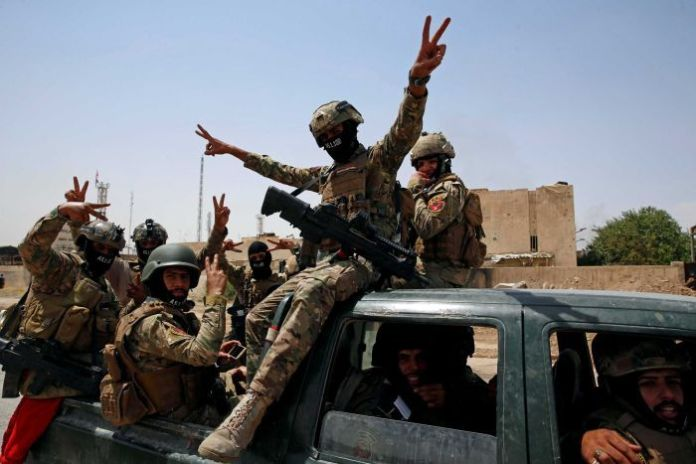 "Members of Iraqi forces make a ""V"" sign as they arrive to take part in a victory celebration."