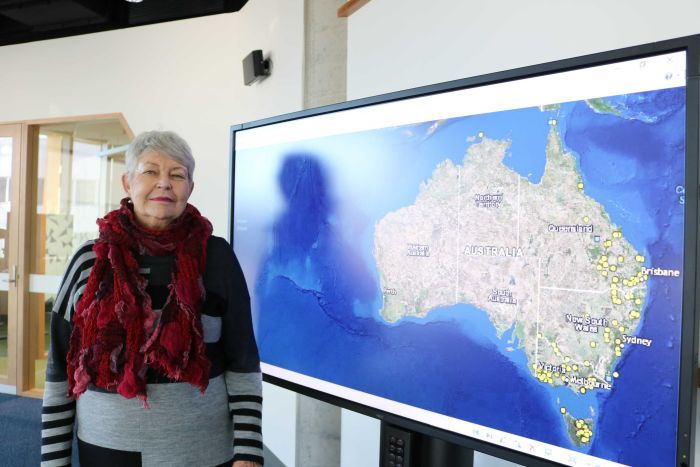 Lyndall Ryan stands next to a screen showing a map that plots massacres of Aboriginal people in the Frontier Wars.