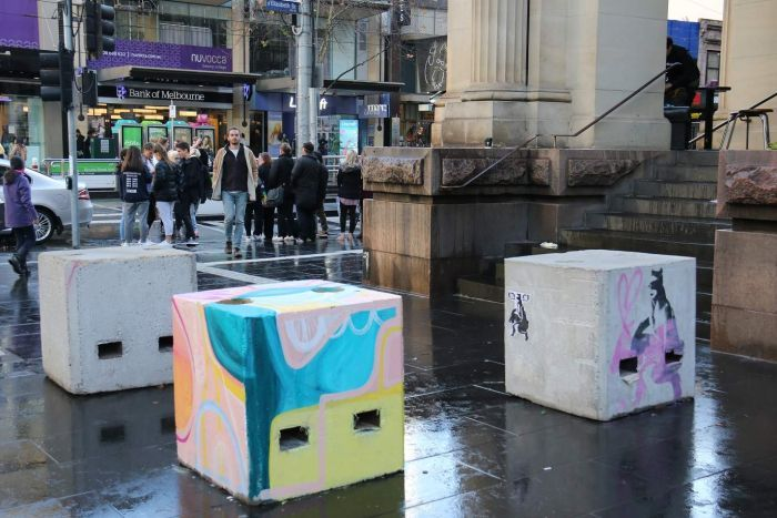 Concrete security bollards in Bourke Street mall painted by street artists.