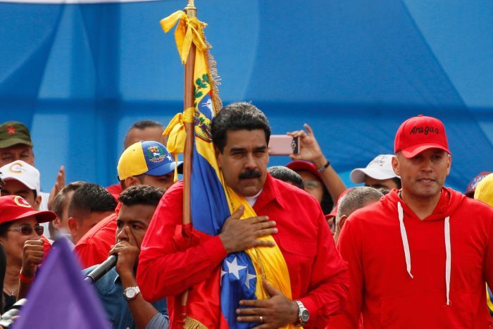 Venezuela's President Nicolas Maduro holds the Venezuelan flag, with his hand on his chest, during a rally in Caracas.